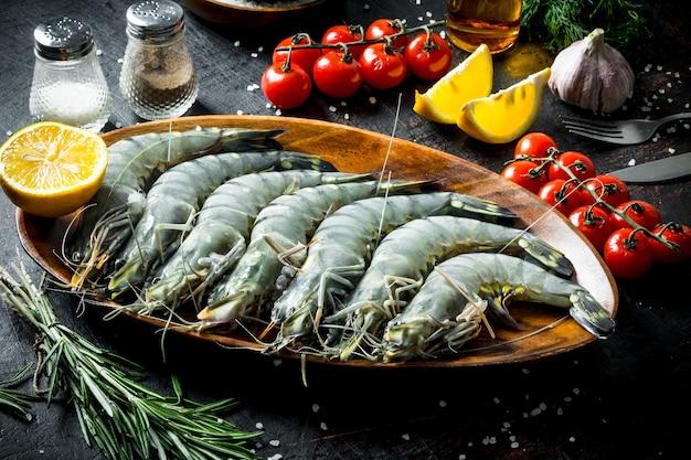 Свежие сырые креветки с помидорами черри, чесноком и нарезанным лимоном.