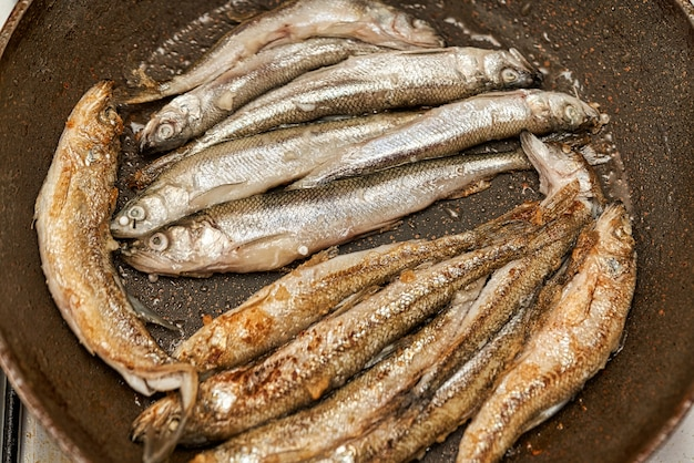 Свежая сырая серебряная рыба корюшка, обжаренная на сковороде