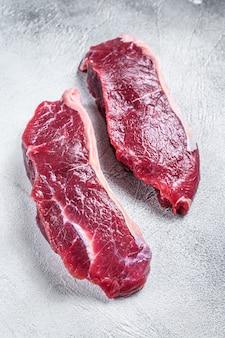 新鮮な生サーロインビーフミートステーキ。白色の背景。上面図。