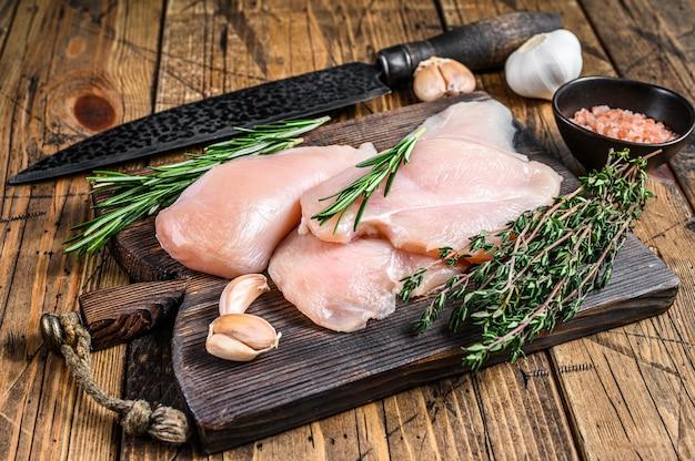 Свежие сырые нарезанные стейки филе куриной грудки на деревянной разделочной доске кухонным ножом. деревянный фон. вид сверху.