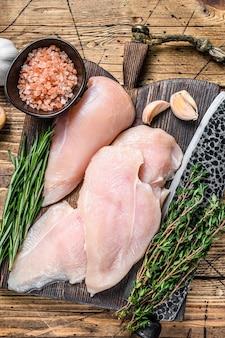 부엌 칼로 나무 커팅 보드에 신선한 원시 얇게 썬 닭 가슴살 필레 스테이크. 나무 배경입니다. 평면도.