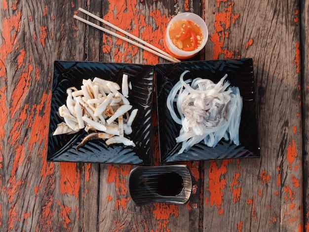 Свежие сырые нарезанные кальмары и кальмары гриль на деревянной доске с соусом из морепродуктов в тайском стиле и японским соевым соусом или сёю