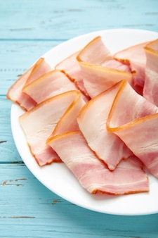 Fresh raw slices bacon on plate on blue wooden background. top view