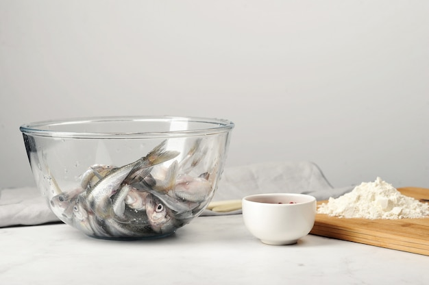 Fresh raw smelt in a deep glass dish is ready for frying in a flour with spices