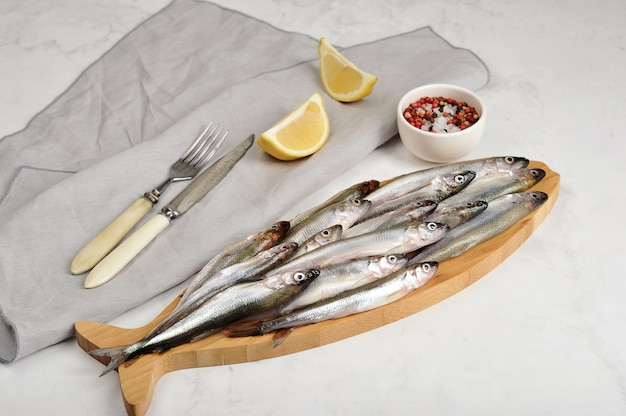 Fresh raw smelt on a wooden board with lemon