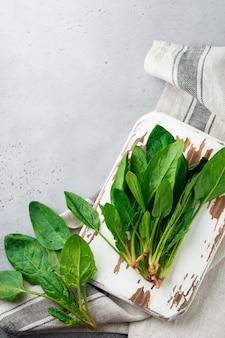 Свежие сырые листья шпината на деревянной деревенской подставке на серой старой бетонной поверхности. ингредиенты для салата