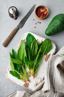 Fresh raw spinach leaves on a wooden rustic stand on a gray old concrete background. ingredients for salad
