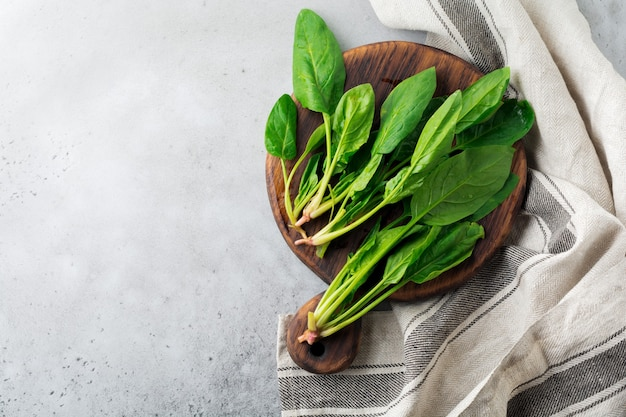Fresh raw spinach leaves on a wooden rustic stand on a gray old concrete surface. ingredients for salad. selective focus. top view.
