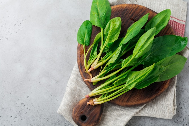 Fresh raw spinach leaves on a wooden rustic stand on a gray old concrete surface. ingredients for salad