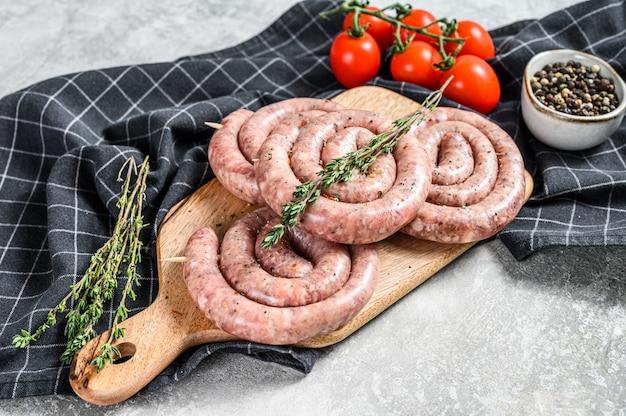 Fresh raw spiral chicken sausages. gray background.