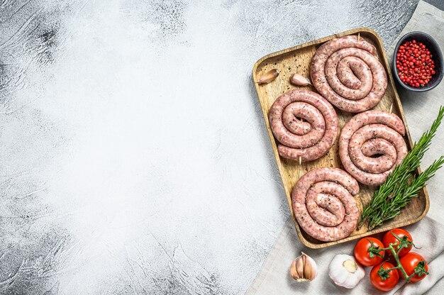 Свежие сырые спиральные свиные колбаски на деревянном подносе