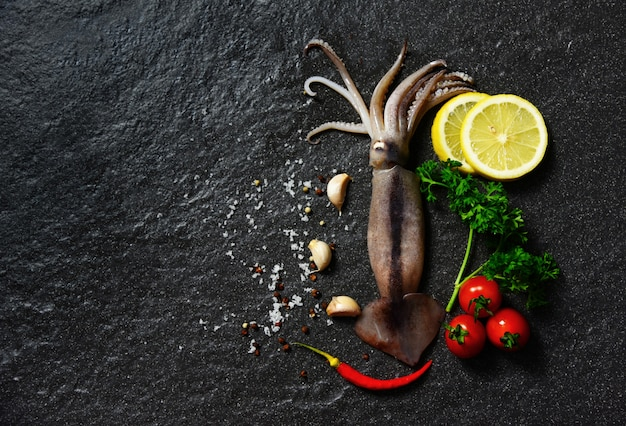 Fresh raw squid seafood herbs and spices with lemon tomato garlic