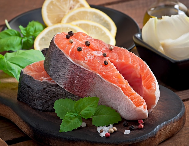 Fresh and raw steaks trout on a wooden cutting board with sliced lemon, rosemary and pepper