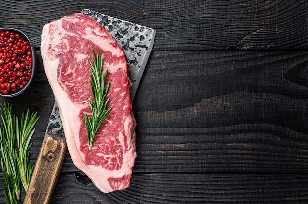 Fresh raw striploin beef steak on a butcher meat cleaver