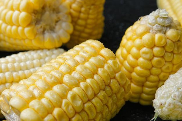 Fresh raw sweet corn cobs on black background. close-up.