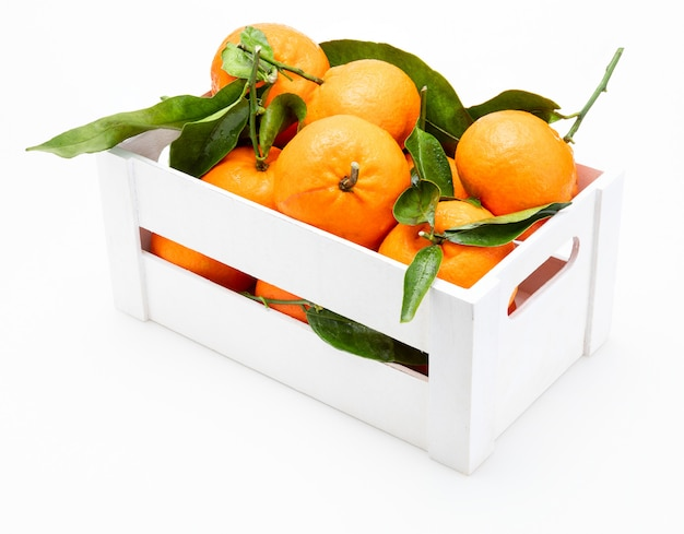 Fresh and raw tangerines with green leaves in wooden box. isolated