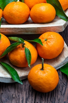 Fresh and raw tangerines with green leaves