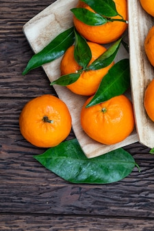 Fresh and raw tangerines with green leaves.