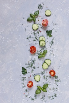 Fresh raw tomatoes, cucumbers and seasonal greens. top view, close-up on vintage gray table