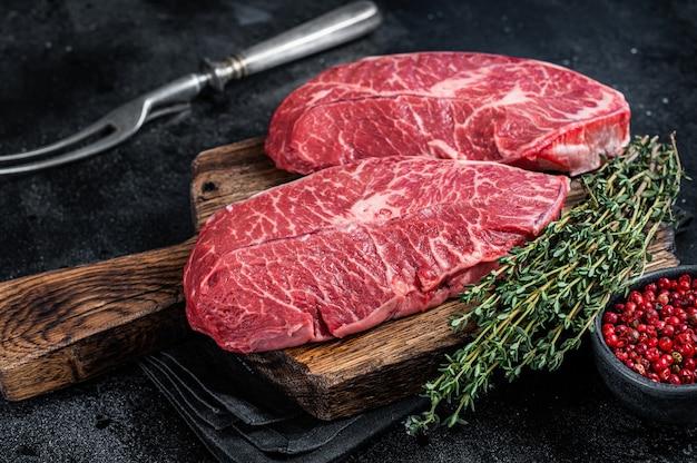 정육점 커팅 보드에 신선한 생 톱 블레이드 또는 평평한 철 쇠고기 고기 스테이크. 검은 배경. 평면도.