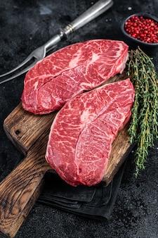 Свежие сырые стейки из говядины или плоские стейки на разделочной доске мясника. вид сверху.