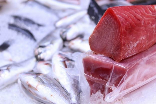 Свежий сырой тунец на льду, сырой стейк из тунца