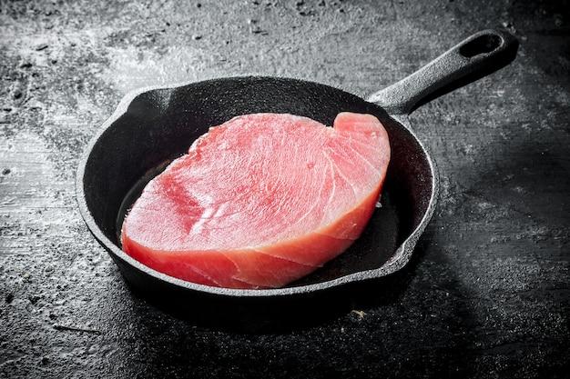 Свежий сырой стейк из тунца в сковороде на черном деревенском столе.