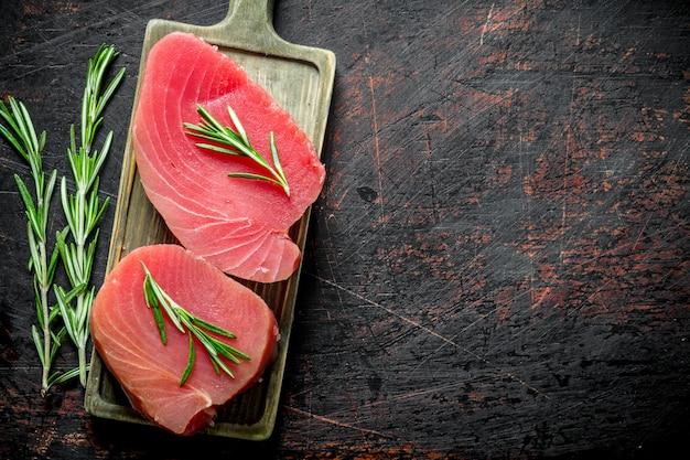 Стейк из свежего сырого тунца на разделочной доске с розмарином. на темном деревенском фоне