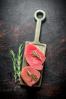 Стейк из свежего сырого тунца на разделочной доске с розмарином. на темной деревенской поверхности