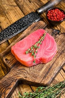 Свежий сырой стейк из тунца на деревянной разделочной доске с ножом.