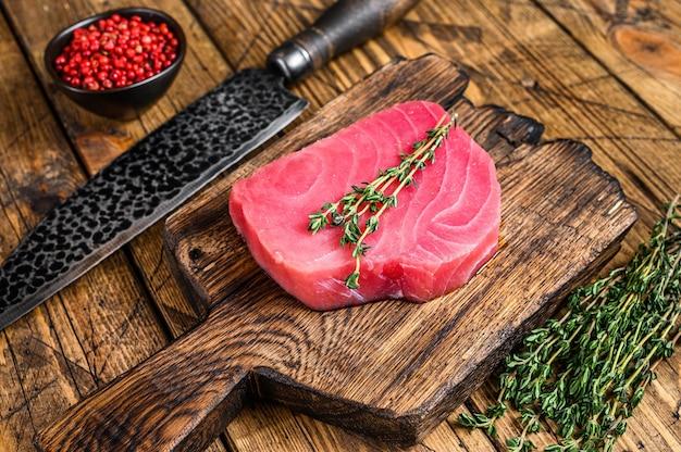 Свежий сырой стейк из тунца на деревянной разделочной доске с ножом