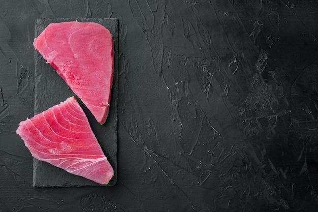 Набор свежего сырого стейка из тунца, на каменной доске, на черном камне