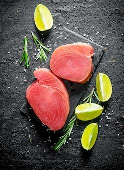 Свежий сырой стейк из тунца с лаймом и розмарином на черном деревенском столе.