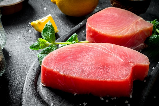 Стейк из свежего сырого тунца с мятой и лимоном. на темной деревенской поверхности