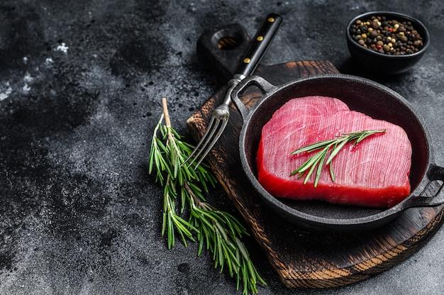 Свежий сырцовый стейк из тунца с розмарином на сковороде. черный фон. вид сверху. скопируйте пространство.