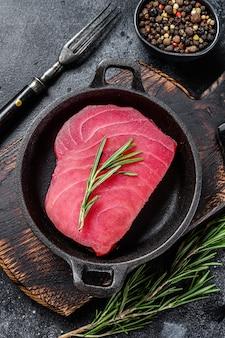 Свежий сырой стейк из тунца с розмарином на сковороде.
