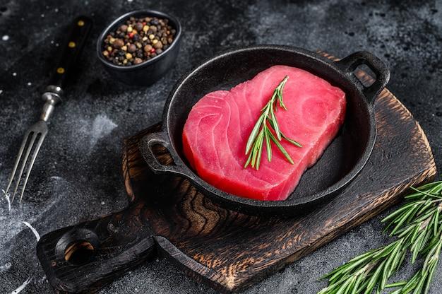 Стейк из свежего сырого тунца с розмарином на сковороде