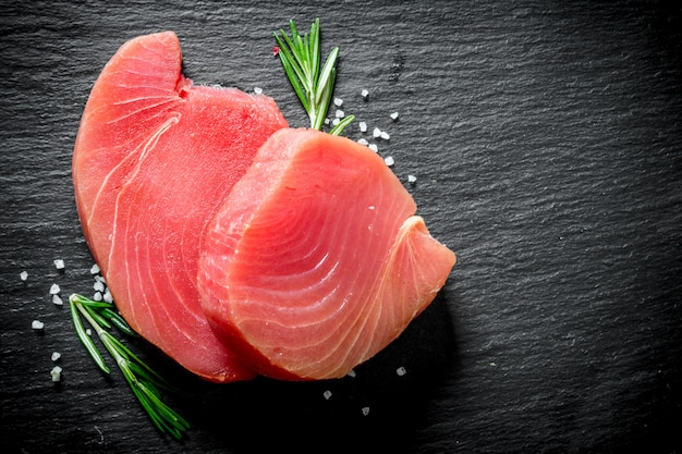 Fresh raw tuna steak with rosemary.