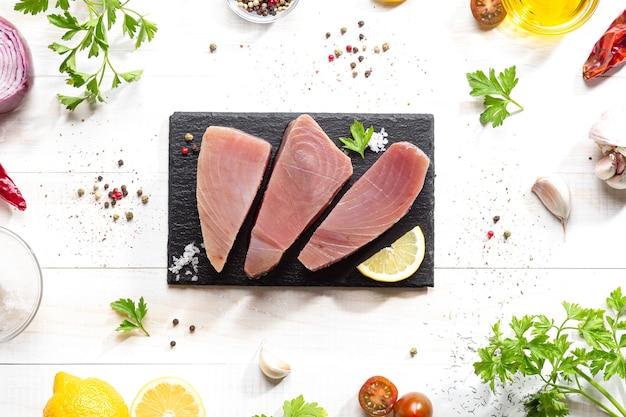 Fresh raw tuna steaks on black slate plate on white background