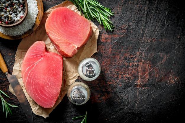 Свежий сырой тунец с розмарином и специями на темном деревенском столе.