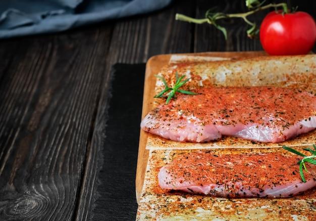 Bistecca di tacchino crudo fresco, deliziosa bistecca succosa con verdure e spezie su una superficie di pietra scura