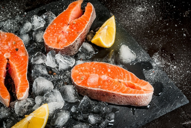 Fresh raw unprepared fish salmon trout steaks on a black slate board with ice salt pepper and lemon for cooking. ingredients of a healthy diet.