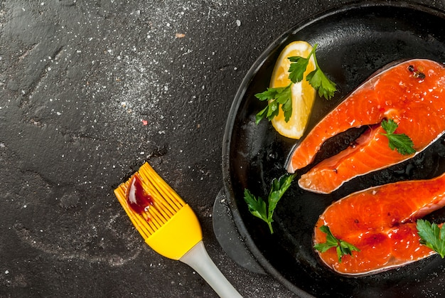 Fresh raw unprepared fish salmon or trout steaks in a skillet for cooking with salt pepper lemon and barbecue sauce for grilling. on black stone concrete table top close view