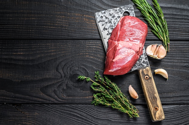 Fresh raw veal chop meat steak on a meat cleaver.