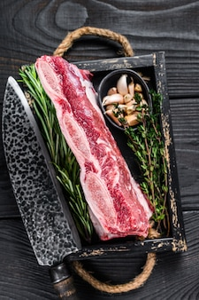 Fresh raw veal short ribs in a wooden tray with herbs. black wooden background. top view.