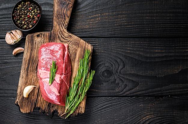 木製のまな板に新鮮な生の子牛のサーロインミートステーキ
