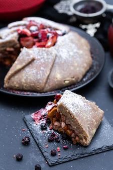 Fresh raw vegan nectarine pie on a dark tabletop