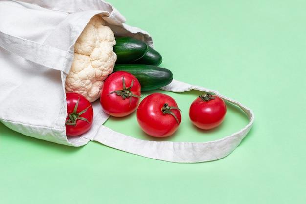 Свежие сырые овощи, помидоры, огурцы, цветная капуста из магазина в тканевом натуральном эко многоразовом льняном пакете