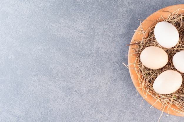 나무 그릇에 신선한 원시 흰색 닭고기 달걀입니다.