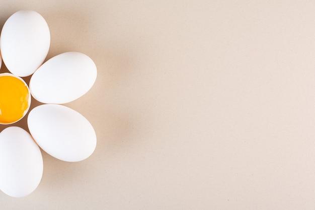 신선한 원시 흰색 닭고기 달걀은 베이지 색 테이블에 배치됩니다.
